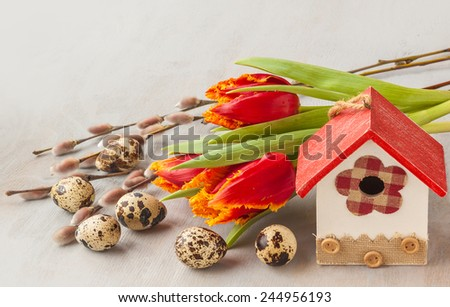 Easter bouquet of daffodils, tulips and willow twigs next to starling house decorative and quail eggs. - stock photo