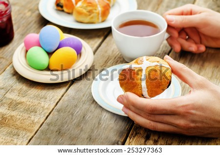 Easter Breakfast. Man holding the bun with a cross and a cup of tea. tinting. selective focus - stock photo
