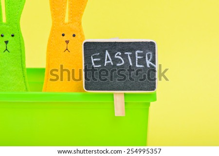 Easter Bunnies in flower pot with black board on yellow paper background - stock photo