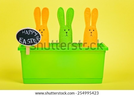 Easter Bunnies in flower pot with chalkboard on yellow paper background - stock photo