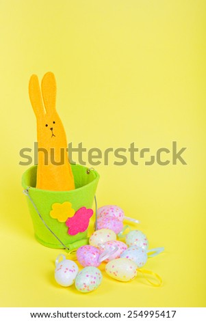 Easter Bunny in bucket and eggs on yellow paper background - stock photo