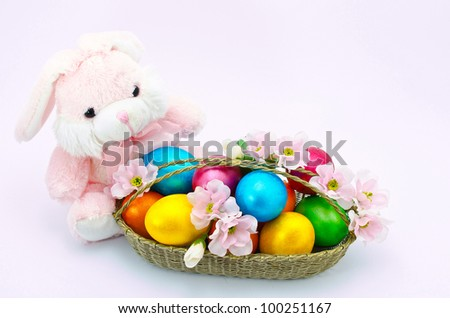 Easter bunny toy with the basket with flowers and color eggs, isolated on a white background - stock photo