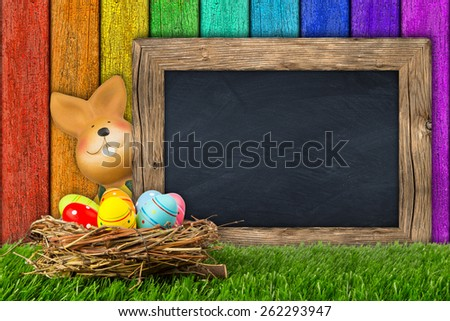 easter bunny with chalkboard on colorful background - stock photo