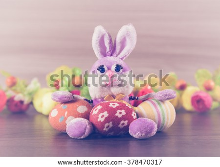 Easter bunny with eggs on a wooden background. - stock photo