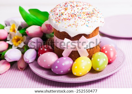 Easter cake and colorful polka dot eggs on the plate and flowers on the foreground - stock photo
