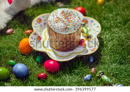 Easter cake and Easter eggs and candies over green grass. Selective shallow focus - stock photo