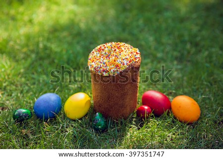 Easter cake and Easter eggs  on green grass. Selective shallow focus - stock photo