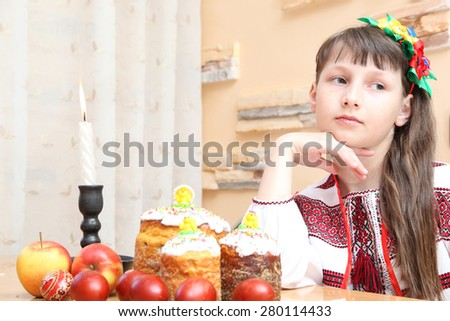 Easter cake and eggs. Girl in Ukrainian embroidery celebrates Easter - stock photo