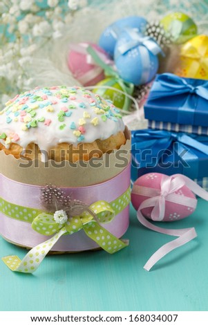 Easter cake, colored eggs and presents in blue boxes (vertical shot) - stock photo
