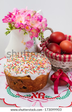Easter cake, jug with flowers and painted eggs on a embroidered napkin - stock photo
