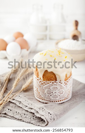 Easter cake, kulich with glaze, eggs on a white wooden background/ traditional Russian pastry. - stock photo
