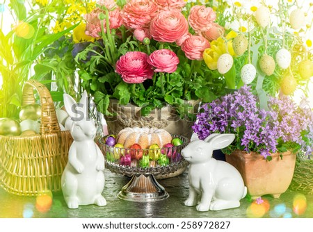Easter cake, spring flowers, eggs and bunny. Festive home decoration. Retro style toned picture with light leaks - stock photo