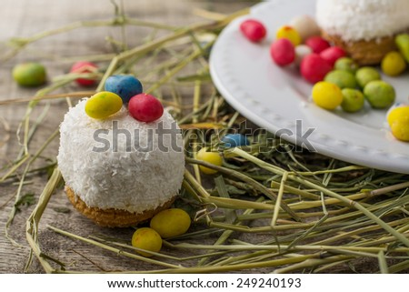 Easter cake with coconut decorated with colored jelly beans in the shape of Easter eggs on a wooden background with a straw. Rustic style. selective Focus - stock photo