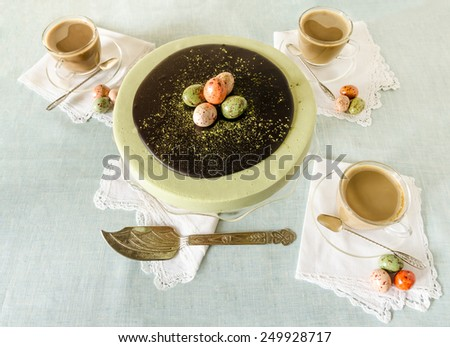 Easter cake with tea matcha decorated chocolate eggs. Near cup of coffee.  - stock photo