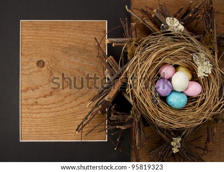 easter candy in a nest with a frame on wooden background - stock photo