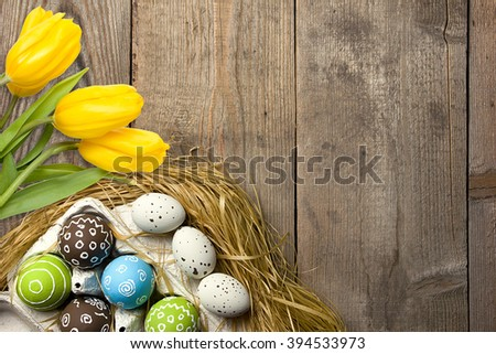 Easter card with colorful eggs in nest and yellow tulips over wooden background. Top view with copy space - stock photo