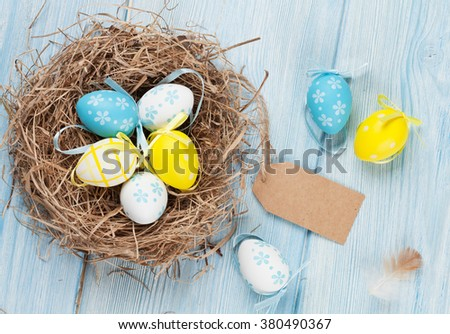 Easter card with eggs in nest over wood. Top view with tag for copy space - stock photo