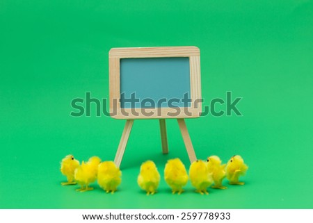 Easter chicks gathered around blue pastel chalkboard on green background - stock photo