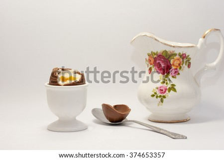 Easter chocolate egg in egg cup next to egg shell in a spoon on the white background with jug - stock photo