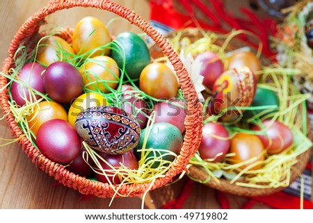 Easter colorful painted eggs in basket on table - stock photo