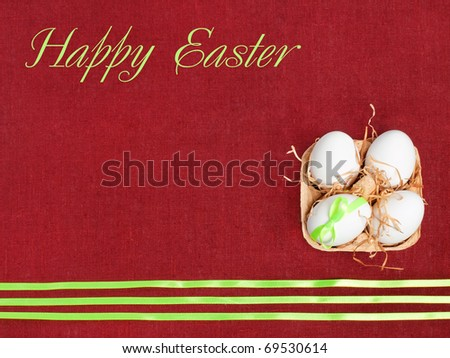 Easter composition:  four white eggs on wine red flax background decorated with green ribbons (with space for text) - stock photo