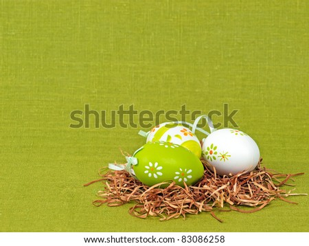 Easter composition: nest with three colorful eggs on a green flax background (with space for text) - stock photo