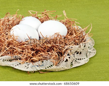 Easter composition: nest with three white eggs on green flax background with lace decoration - stock photo