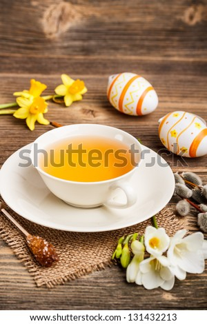 Easter composition of tea cup, eggs and flowers on old wooden - stock photo