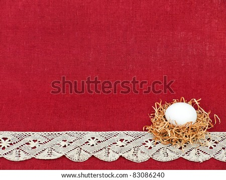 Easter composition: small nest with white egg on wine red flax background decorated with lace (with space for text) - stock photo