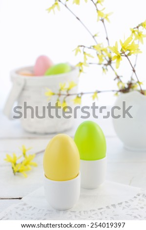 Easter composition with eggs and flowering branches on wooden table  - stock photo