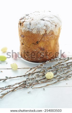 Easter composition with eggs holiday cake and willow branches on wooden table - stock photo