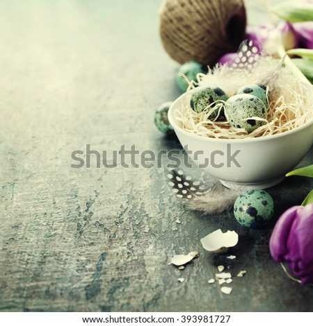 Easter composition with tulips, eggs and nest on vintage wooden background - stock photo