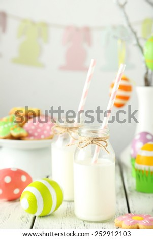 Easter cookies with bottle of milk on white wooden background - stock photo
