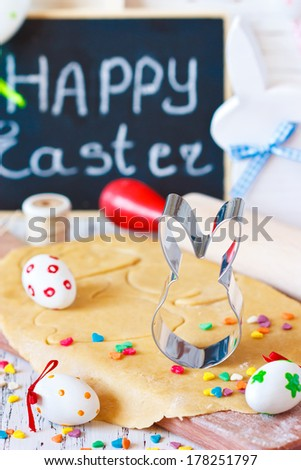 Easter cooking. Bunny cookie cutter on a sweet dough and colorful chocolate eggs. - stock photo