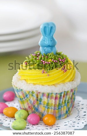 Easter cupcake. Angel food cupcake with vanilla frosting decorated with a candy bunny. - stock photo