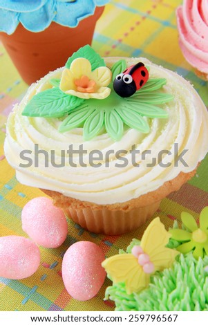 Easter cupcake with a flower and ladybug made of fondant. - stock photo
