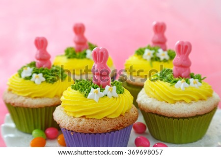 Easter cupcakes decorated with chocolate bunnies and yellow buttercream. - stock photo