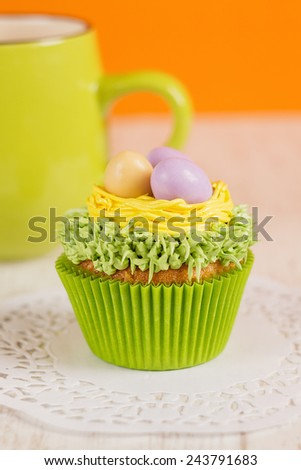 Easter cupcakes decorated with eggs in nest. Orange background with green mug. Shallow focus - stock photo