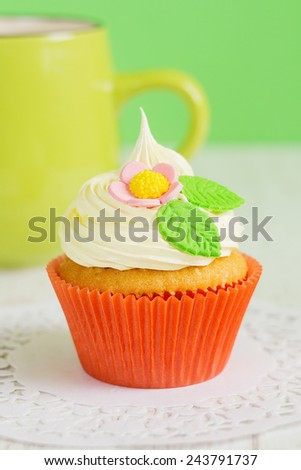 Easter cupcakes decorated with flowers on green background with coffee mug. Shallow focus - stock photo
