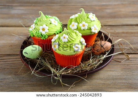 Easter cupcakes with flowers on hay - stock photo