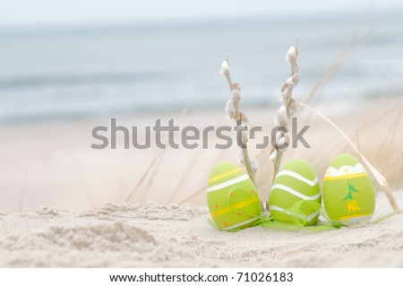 Easter decorated eggs and catkin on sand. Beach and ocean in the background - stock photo