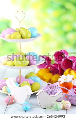 Easter decoration, eggs and tulips on table on natural background - stock photo