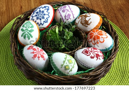 Easter decoration - embroidered eggs in rattan basket on green placemats - stock photo