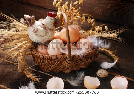 easter decoration of hen figurine in wicker basket with eggs on wooden background - stock photo