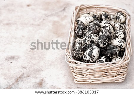 Easter decoration. Quail eggs in the basket on the marmur background. Quails Eggs in old rustic retouch. background with selective focus and diffused natural light. murmur - stock photo