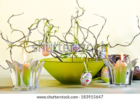 Easter decoration with branches, green bowl and candles - stock photo