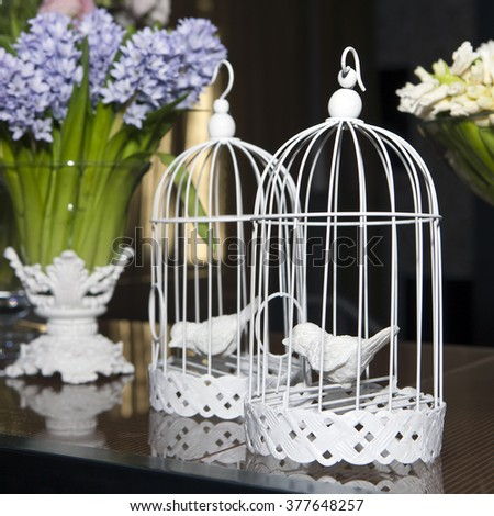 Easter decoration with cage, birds and flowers - stock photo