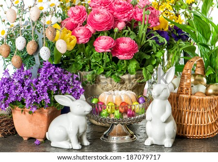 easter decoration with cake, spring flowers, eggs and bunnies - stock photo