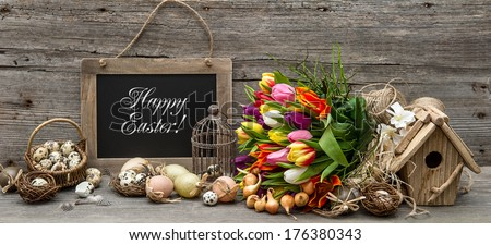 easter decoration with eggs and tulip flowers. vintage style background with sample text Happy Easter!  - stock photo
