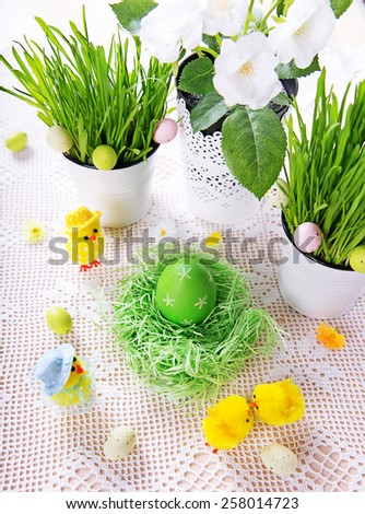 Easter decoration with green grass,flowers,eggs and chickens, top view - stock photo